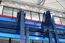Vertical manifolds which unload chip on a main overhead line of the centralized overhead swarf transport serving vertical turning lathes in the workshop of a manufacturing company of railroad components.