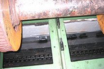 Detail of a screw evacuator serving a lathe in the pit for the re-profiling of wheels at a railroad workshop.